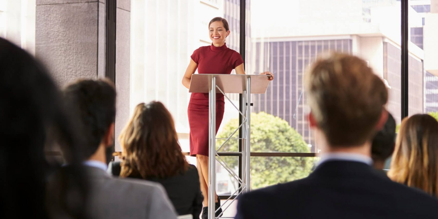 young-woman-leaning-on-lectern-presenting-P3WXMXF
